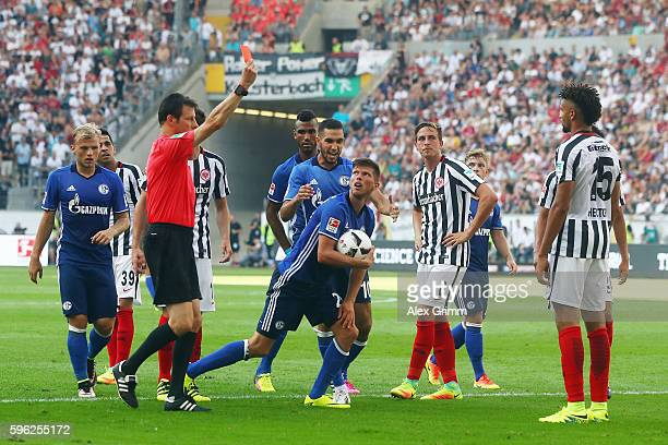 Referee Wolfgang Stark shows the red card to Michael Hector of Frankfurt during the Bundesliga match between Eintracht Frankfurt and FC Schalke 04 at...
