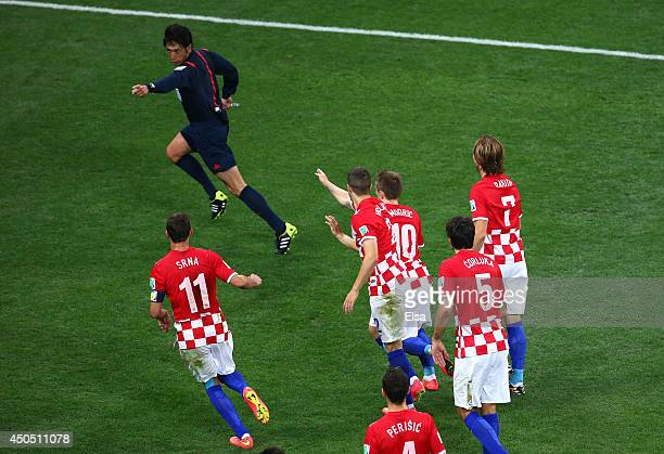 Referee Yuichi Nishimura is pursued by Darijo Srna Sime Vrsaljko Vedran Corluka and Dejan Lovren of Croatia after awarding a penalty kick and giving...
