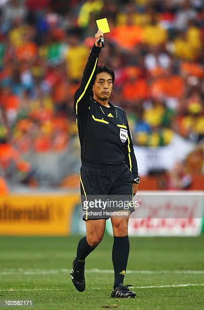 Referee Yuichi Nishimura issues a yellow card to John Heitinga of the Netherlands during the 2010 FIFA World Cup South Africa Quarter Final match...