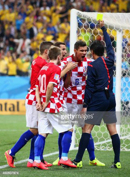 Referee Yuichi Nishimura shows Dejan Lovren of Croatia a yellow card in the second half during the 2014 FIFA World Cup Brazil Group A match between...
