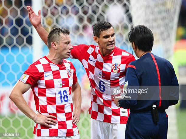 Referee Yuichi Nishimura speaks with Ivica Olic and Dejan Lovren of Croatia after giving Lovren a yellow card and awarding a penalty kick in the...