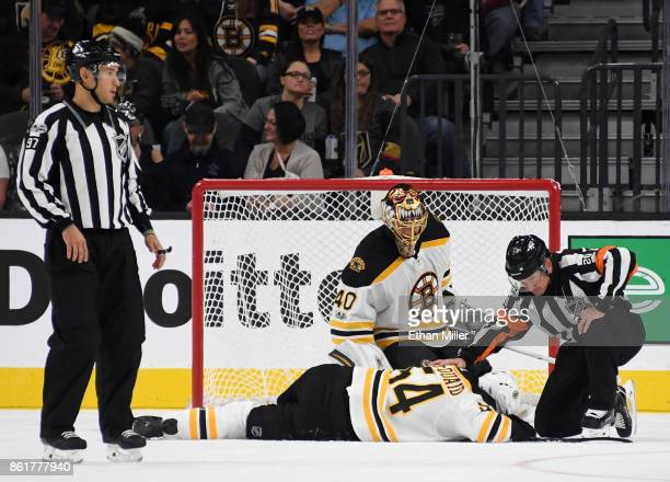 Referees and Tuukka Rask of the Boston Bruins tend to Adam McQuaid of the Bruins after he was hit by a shot from Colin Miller of the Vegas Golden...