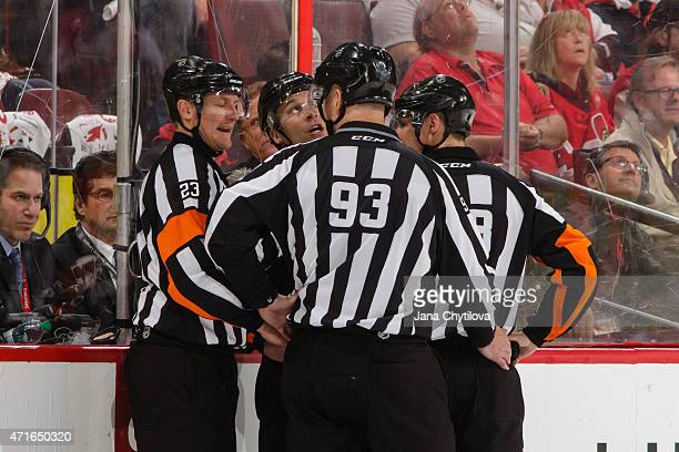 Referees Brad Watson and Chris Lee and linesman Brian Murphy Mark Shewchyk confer during a game between the Ottawa Senators and the Montreal...