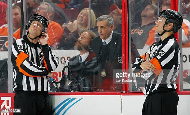 Referees Chris Lee and Ghislain Hebert watch the replay of a disputed third period goal by Karl Alzner of the Washington Capitals against the...