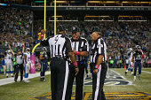 Referees confer after the ball was batted out of the end zone by outside linebacker KJ Wright of the Seattle Seahawks following a fumble by wide...