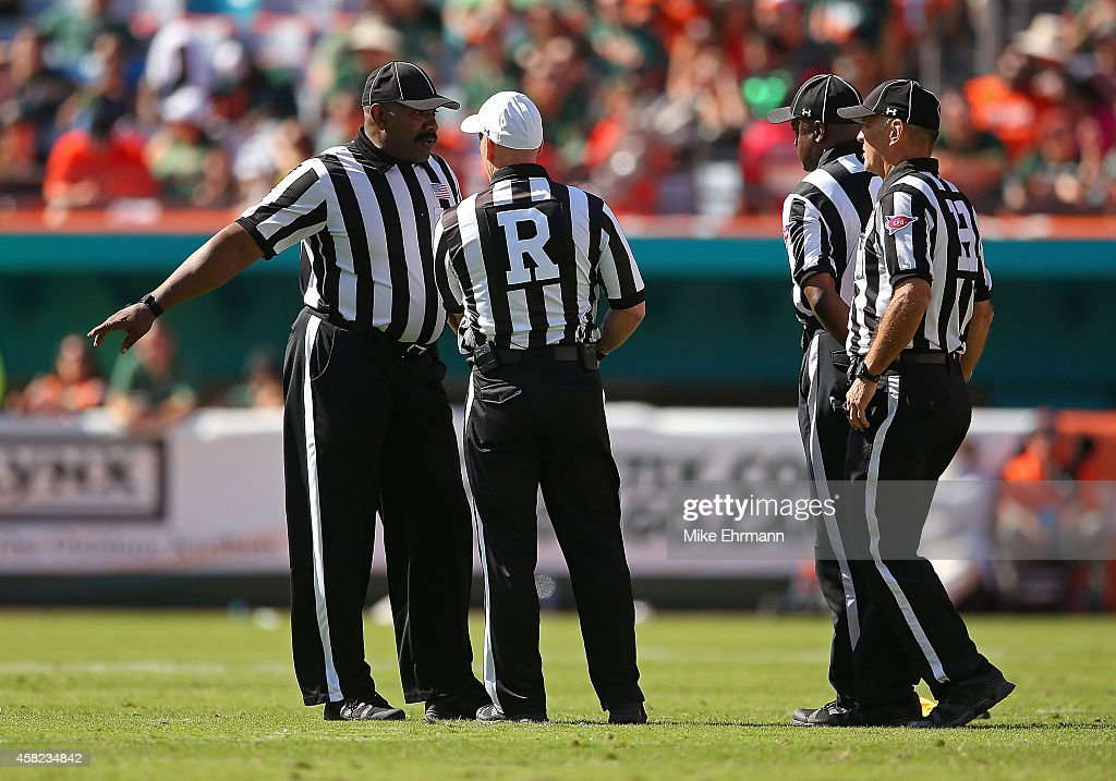 Referees discuss a play during a game between the Miami Hurricanes and the North Carolina Tar Heels at Sun Life Stadium on November 1, 2014 in Miami Gardens, Florida.