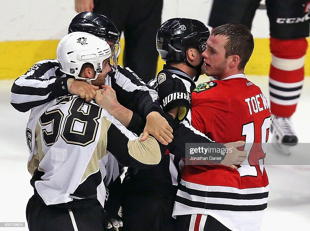 Referees get between Kris Letang #58 of the Pittsburgh Penguins and Jonathan Toews #19 of the Chicago Blackhawks during an altercation in the third period at the United Center on January 6, 2016 in Chicago, Illinois. The Blackhawks defeated the Penguins 3-1.