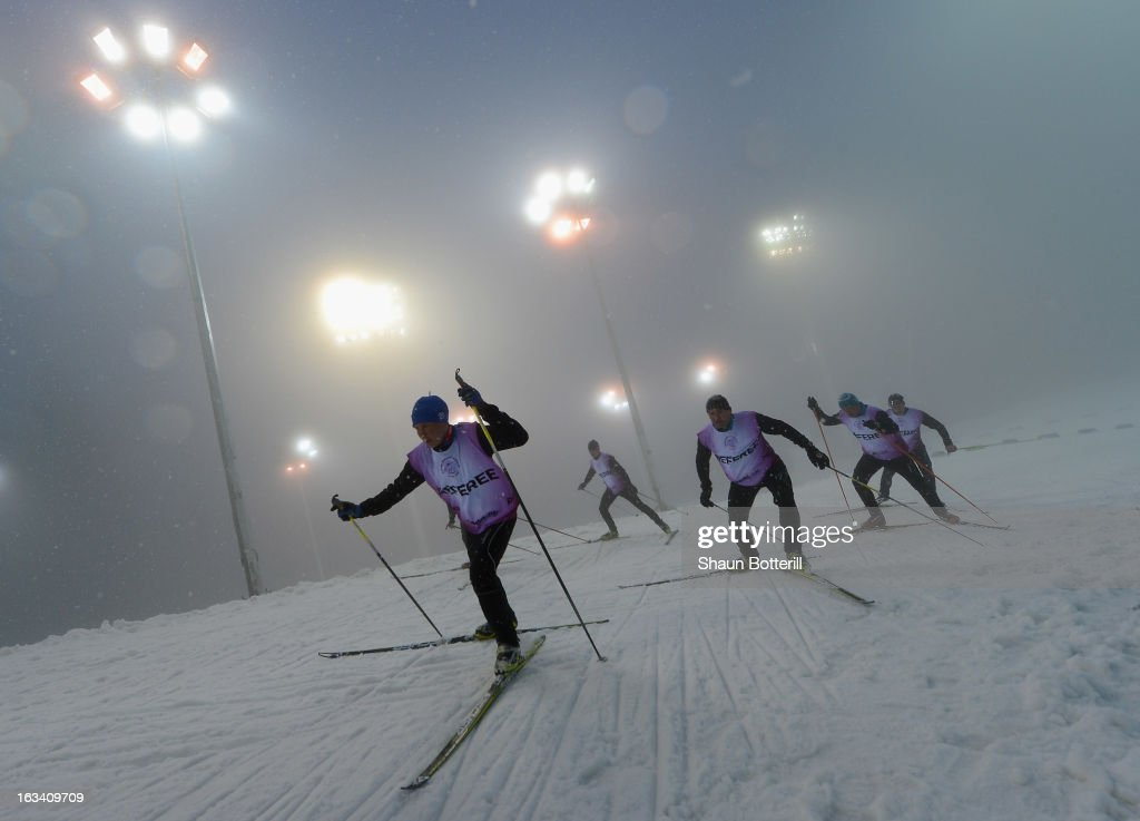 Referees inspect the course in the fog before the Women's 7.5km Sprint event the at Biathlon & Ski Complex on March 9, 2013 in Sochi, Russia.