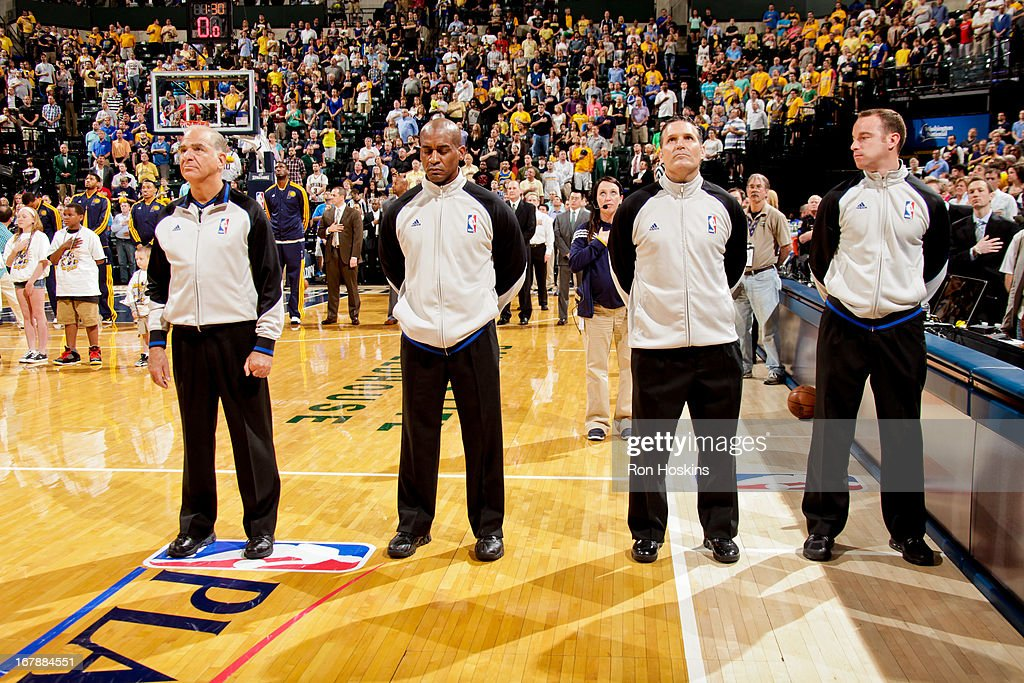 Referees listen to the National Anthem before officiating between the Atlanta Hawks and Indiana Pacers in Game Five of the Eastern Conference Quarterfinals during the 2013 NBA Playoffs on May 1, 2013 at Bankers Life Fieldhouse in Indianapolis, Indiana.