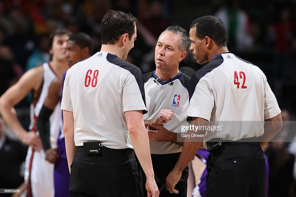 Referees Marat Kogut Jason Phillips and Eric Lewis huddle on the court during the game between the Sacramento Kings and the Milwaukee Bucks on...