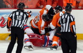Referees Paul Devorski and Francis Charron look on as Brayden Schenn and Vincent Lecavalier of the Philadelphia Flyers fight John Erskine of the...