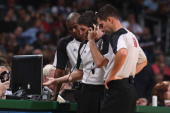 Referees Sean Wright Scott Foster and David Guthrie review a replay during the game between the Charlotte Bobcats and the Milwaukee Bucks on November...