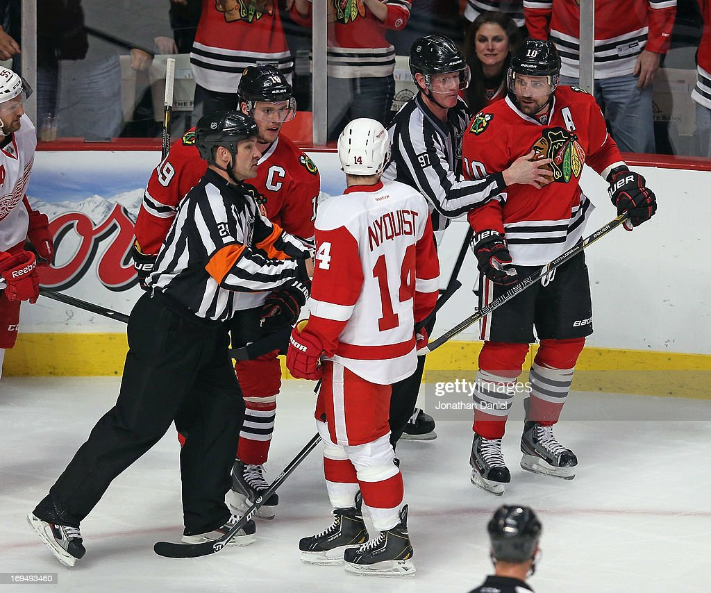 Referees separate Jonathan Toews and Patrick Sharp of the Chicago Blackhawks from Gustav Nyquist of the Detroit Red Wings in Game Five of the Western...