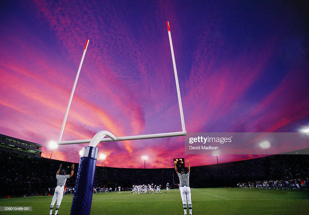 Referees signaling field goal at American football game, sunset