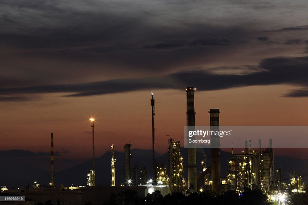 Refiing towers stand illuminated at night at the Motor Oil Hellas SA oil refinery in Agioi Theodoroi, Greece, on Friday, Nov. 23, 2012. Motor Oil Hellas SA Chief Financial Officer Petros Tzanetakis said Greek companies face difficulties in securing financing as foreign banks look at Greece with a 'skeptical eye.' Photographer: Kostas Tsironis/Bloomberg via Getty Images