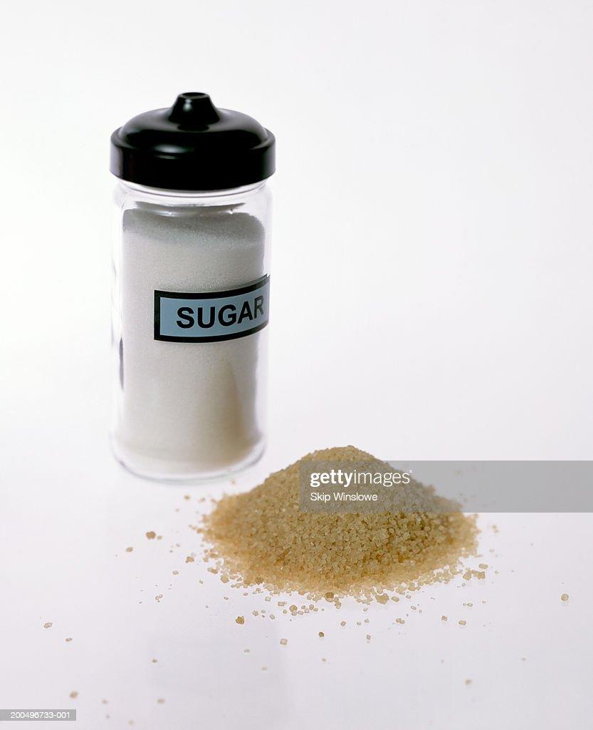 Refined sugar shaker beside pile of raw sugar (still life) : Stock Photo