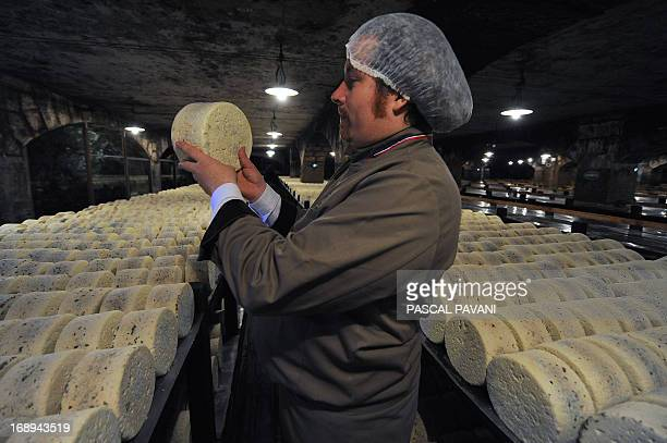 A refiner controls the quality of cheeses at the Roquefort Societe company on May 16 2013 in a cellar at RoquefortsurSoulzon southern France...