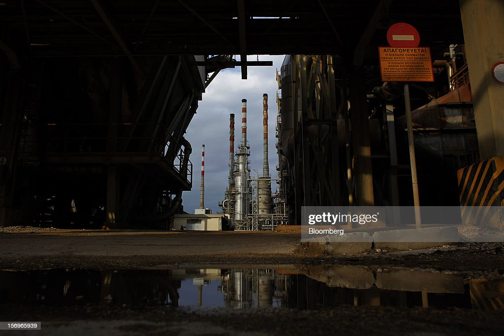 Refining towers are seen beyond factory buildings at the Motor Oil Hellas SA oil refinery in Agioi Theodoroi, Greece, on Friday, Nov. 23, 2012. Motor Oil Hellas SA Chief Financial Officer Petros Tzanetakis said Greek companies face difficulties in securing financing as foreign banks look at Greece with a 'skeptical eye.' Photographer: Kostas Tsironis/Bloomberg via Getty Images