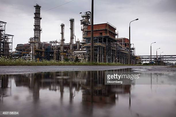 Refining towers reflect in a puddle of rainwater at PKN Orlen SA's oil refinery in Plock Poland on Friday Aug 1 2014 PKN Orlen Poland's biggest oil...