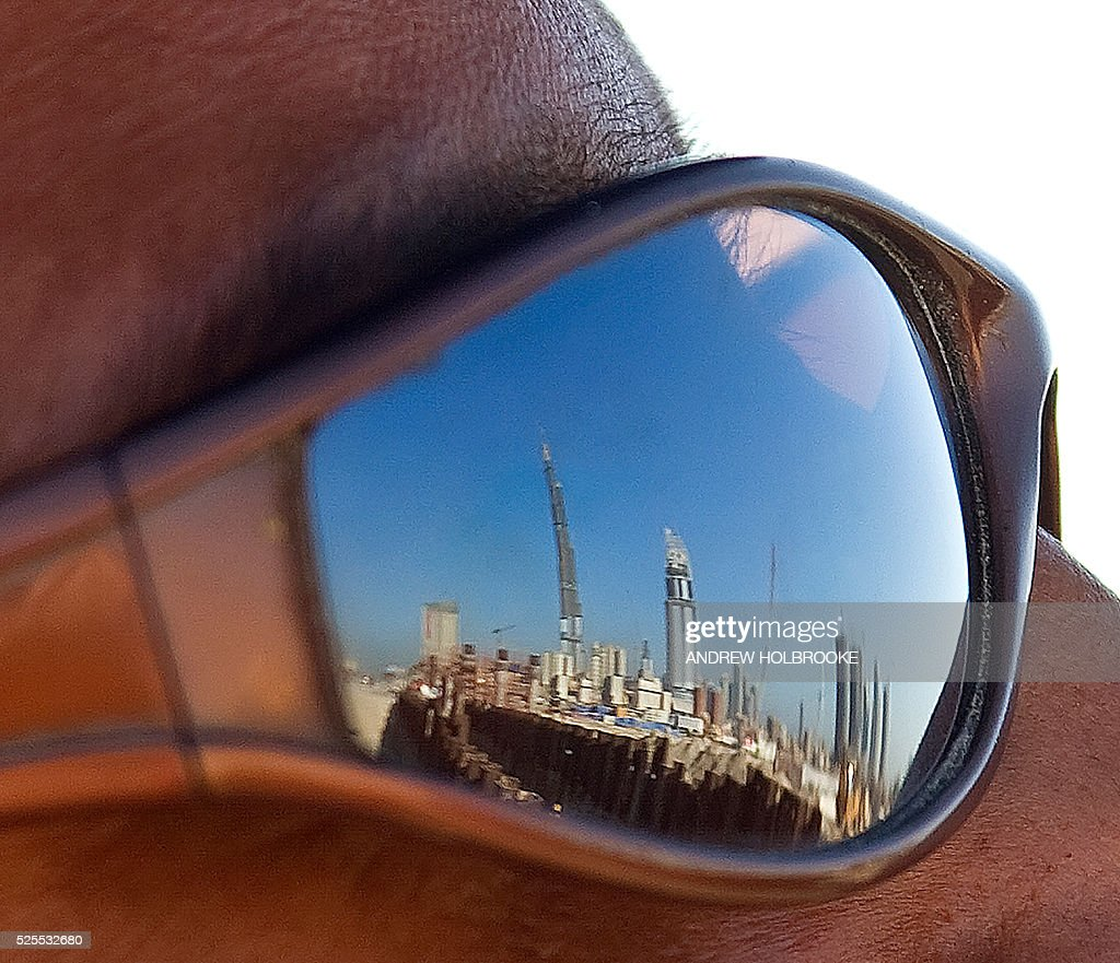 Reflected in a construction worker's sunglasses Dubai is filled with building construction projects including these that surround the construction...