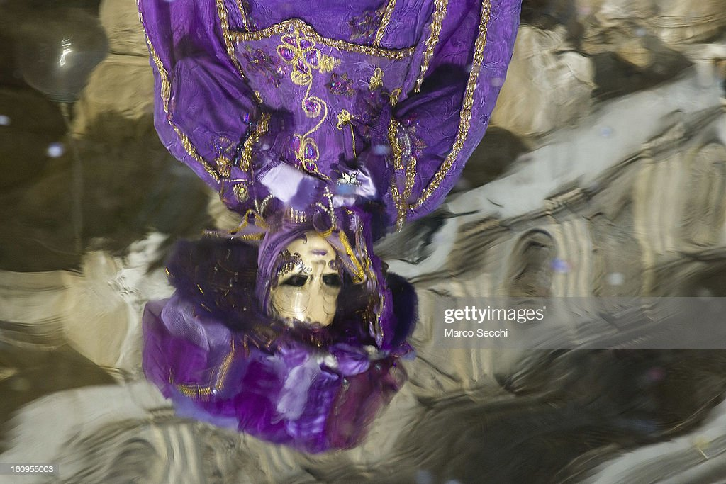 A reflection during high water of a woman wearing a carnival costume is seen while she poses in Saint Mark's Square on February 8, 2013 in Venice, Italy. The 2013 Carnival of Venice runs from January 26 - February 12 and includes a program of gala dinners, parades, dances, masked balls and music events.
