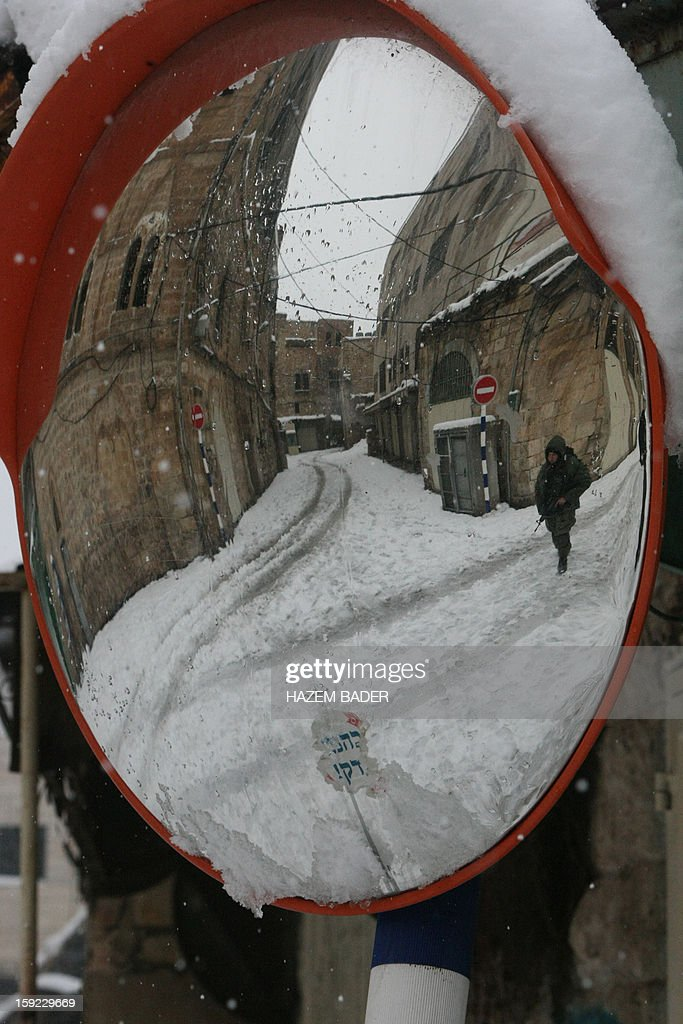 A reflection in a miror shows an Israeli soldier standing guard in front of the Israeli settlers zones despite of the snow on January 10, 2013 in the West Bank city of Hebron. As temperatures plummeted, the bitter winds and rain that have battered the Middle East since Sunday turned into snow, blanketing Jerusalem in white and closing schools and businesses, as much of the transport infrastructure ground to a halt.