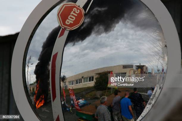 A reflection in a traffic mirror shows a dumspter fire set by employees burning up in black smoke outside the plant of the GMS company on June 27...