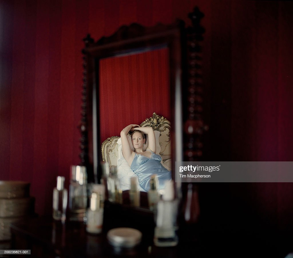 Reflection in dressing table mirror of woman relaxing on bed, portrait : Stock Photo