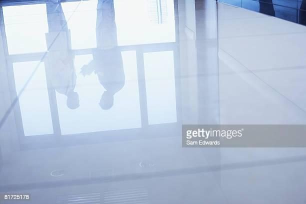 Reflexion in Etage stehen zwei Ärzte im Krankenhaus-Korridor