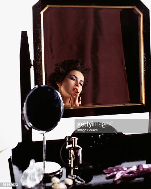 Reflection in mirror of woman putting on lipstick