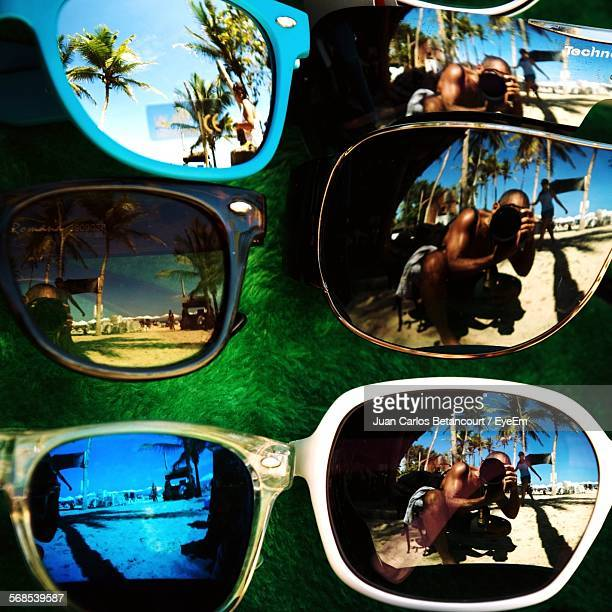 Reflection In Sunglasses Of Man Photographing At Beach