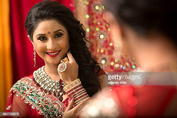 Reflection of a bridal woman in mirror applying lipstick on her lips