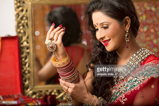 Reflection of a bridal woman in mirror putting on bangles