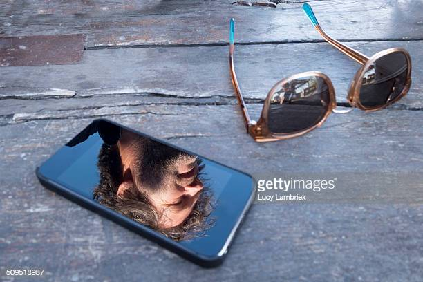 Reflection of a man in his phone