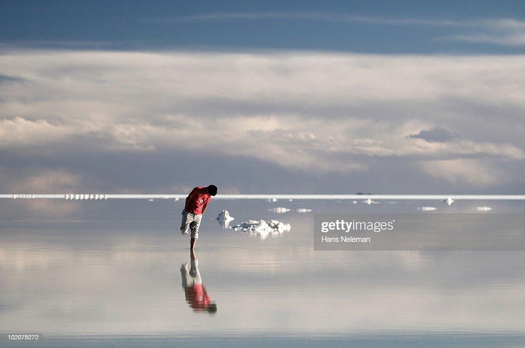 Reflection of a man in water, Salar De Uyuni, Bolivia