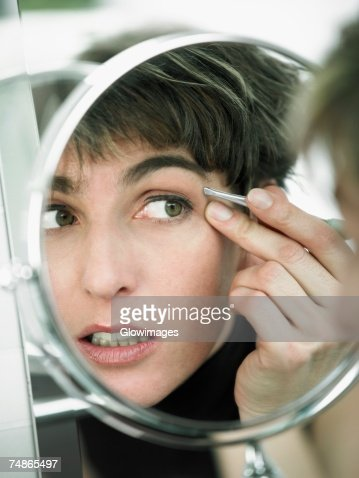 Reflection of a mature woman tweezing her eyebrows in a mirror