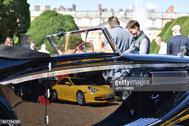 A reflection of a porsche is seen on a vintage car on display at the Concours de Elegance at Hampton Court Palace on September 1 2017 in London...