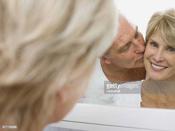 Reflection of a senior man kissing a senior woman in a mirror