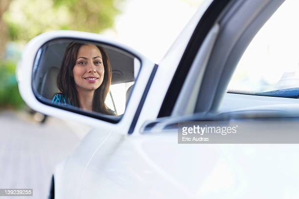 Reflection of a smiling young woman on a car side mirror