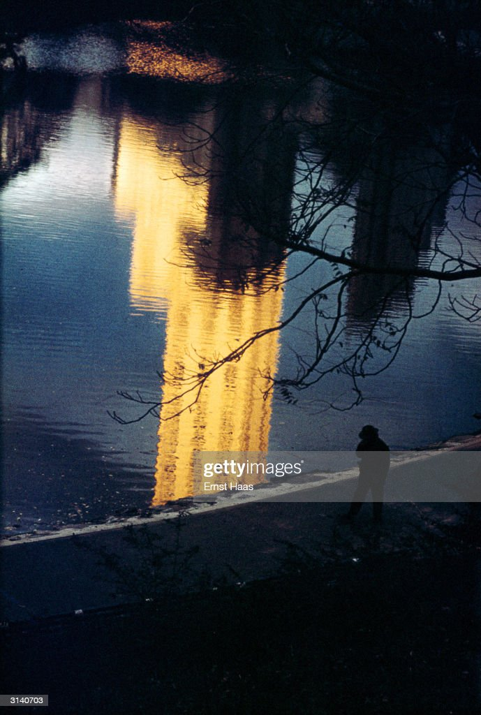 A reflection of a sunlit skyscraper in a lake in New York's Central Park. Colour Photography book.