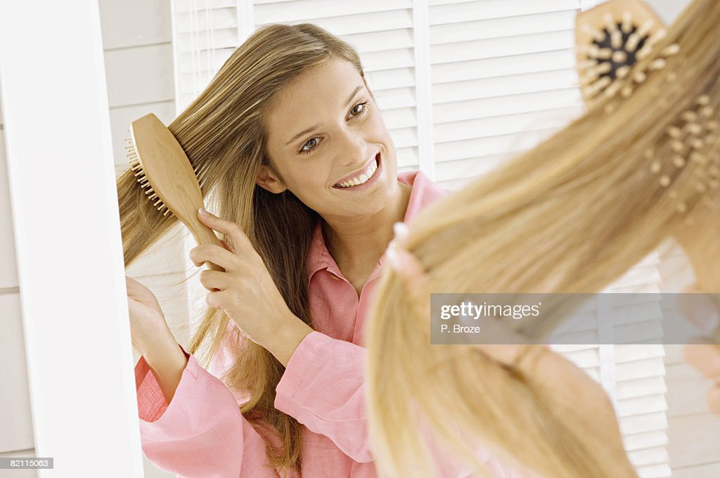 Reflection of a young woman brushing her hair : Stock Photo