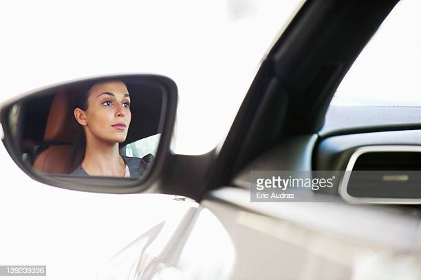 Reflection of a young woman on car's side glass while taking a test drive