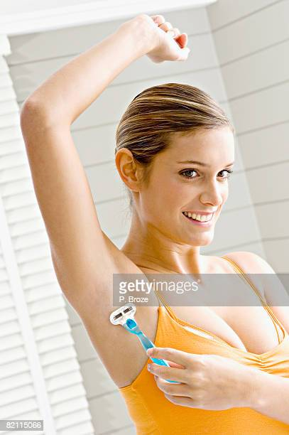 Reflection of a young woman shaving her armpit hair