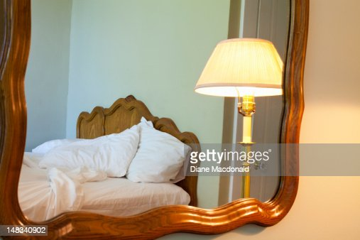 Reflection of an unmade bed and lamp in a mirror : Stock Photo