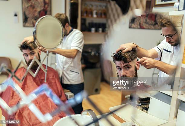 Reflection of barber cutting hair of a customer