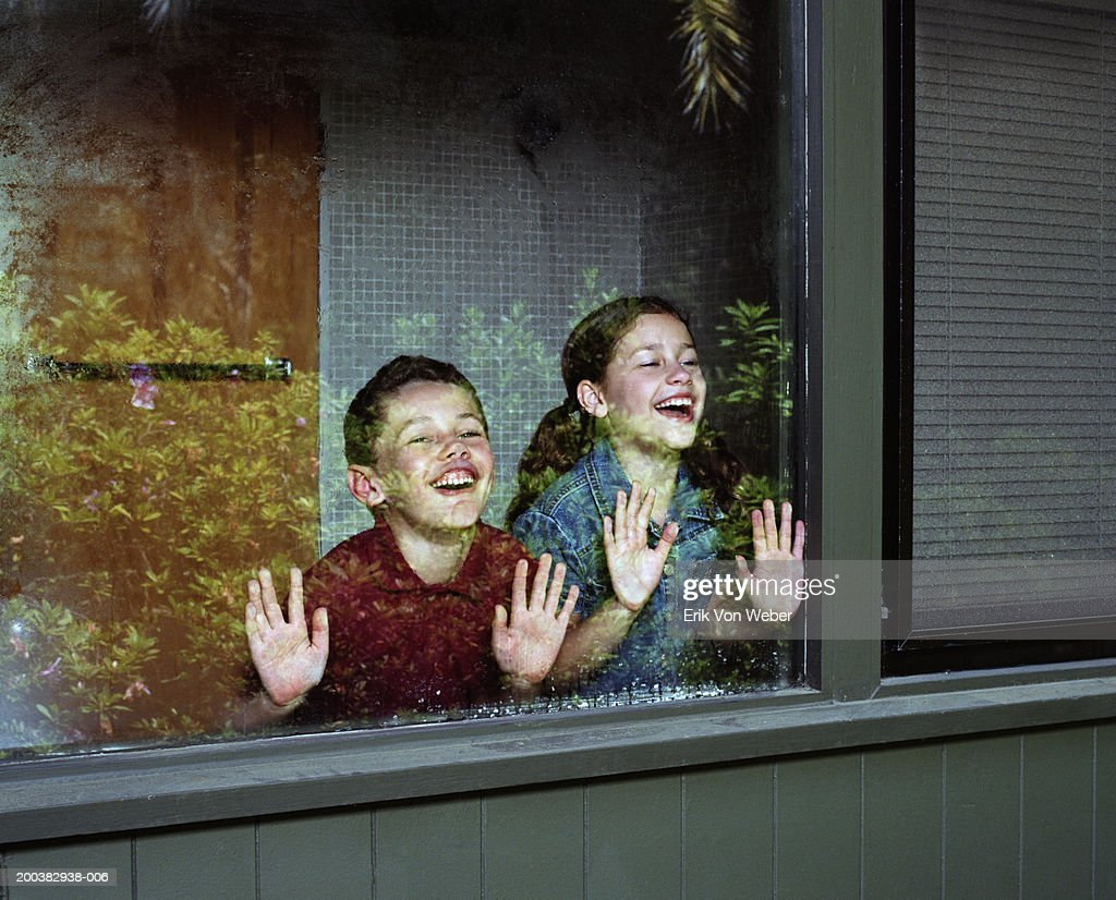 Reflection of boy and girl (6-10) pressing faces against window : Stock Photo