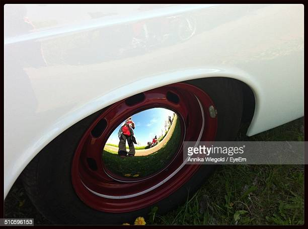 Reflection of boy showing rock sign gesture in cars hubcap