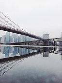 Reflection Of Bridge With City In River