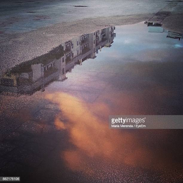Reflection Of Building And Dramatic Sky In Puddle
