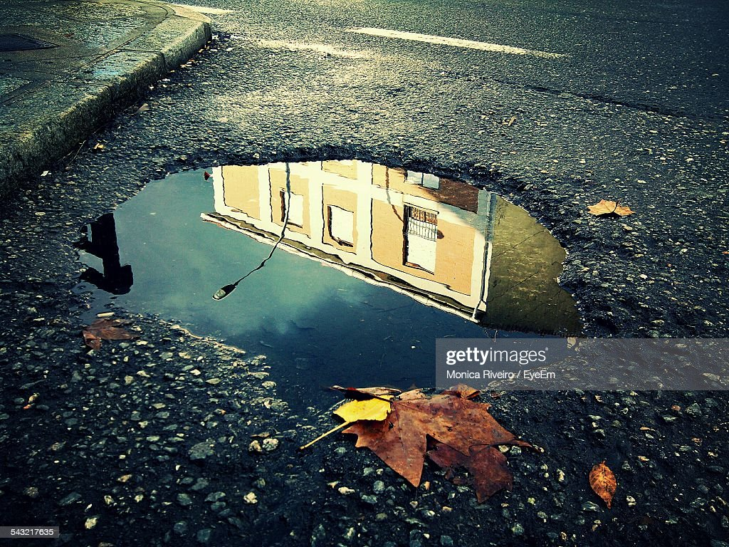 Reflection Of Building In Puddle On Street